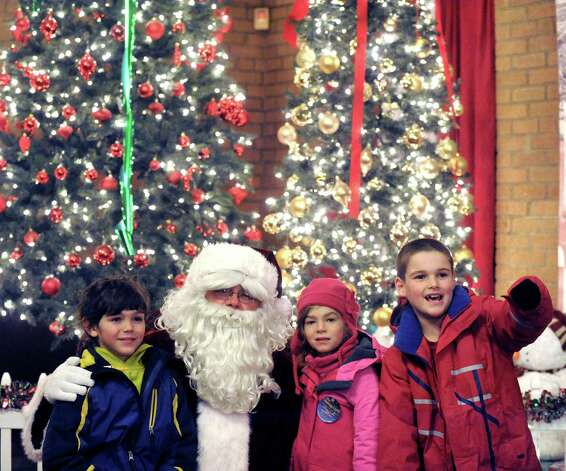 Adam McGowan, left, Reesa McGowan and Jackson Adams, right, all of Delmar get a visit with Santa during the kickoff holiday lights in the park at Washington Park on Tuesday Nov. 18, 2014 in Albany, N.Y. (Michael P. Farrell/Times Union) Photo: Michael P. Farrell / 00029530A