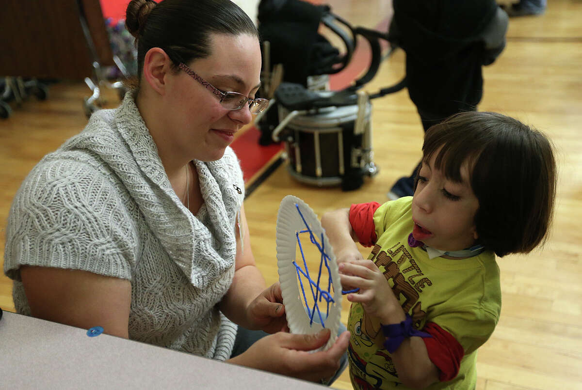 """Pedro Garcia, 9, works on a dreamcatcher with the help of Samantha Baker during the Southside Independent School District's """"Friendship Feast"""" at the ACES Early College Academy. The district's special needs students have been learning about Native American culture."""