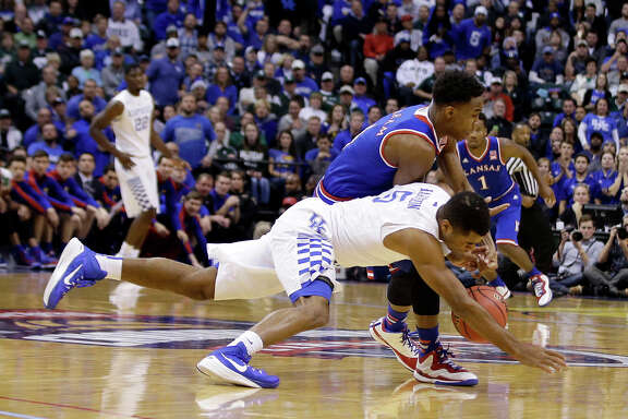 Kentucky's Andrew Harrison (5) hits the floor in a battle for the ball with Kansas' Devonte Graham.