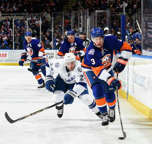 UNIONDALE, NY - NOVEMBER 18: Travis Hamonic #3 of the New York Islanders fights for the puck with Ryan Callahan #24 of the Tampa Bay Lightning in the first period at Nassau Veterans Memorial Coliseum on November 18, 2014 in Uniondale, New York.  (Photo by Alex Goodlett/Getty Images) ORG XMIT: 507047793 Photo: Alex Goodlett / 2014 Getty Images