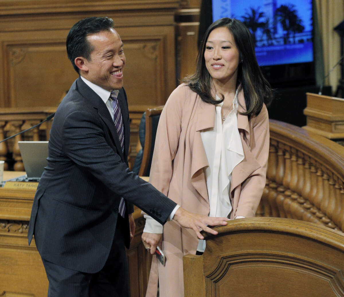 Supervisors President David Chiu walks out with newly elected interim board President Katy Tang.