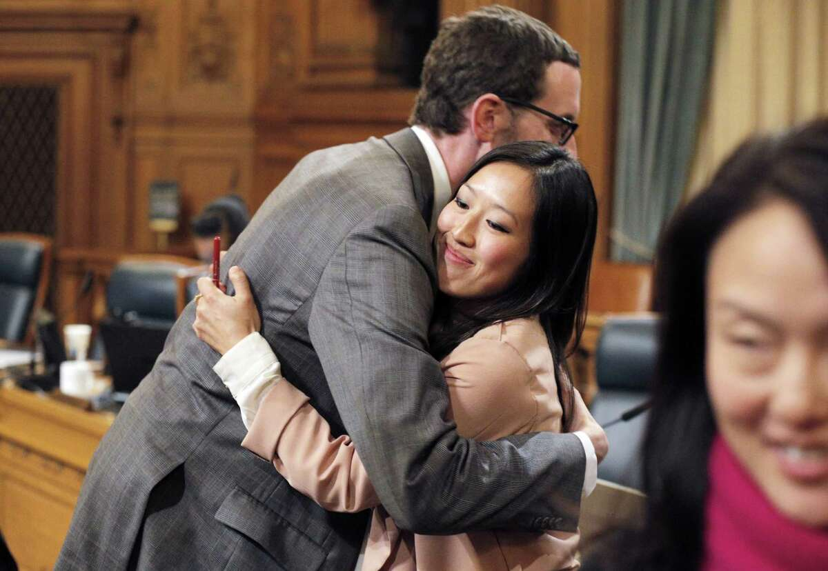 Supervisor Scott Weiner hugs newly-elected interim Board President Katy Tang, right, following Tang's selection on Tuesday. San Francisco Supervisors elected an interim board president on Tuesday, November 18, 2014, naming Katy Tang to replace David Chiu who will be stepping down to join the state assembly in December. The selection took place during the Board of Supervisors meeting at City Hall in San Francisco, Calif.