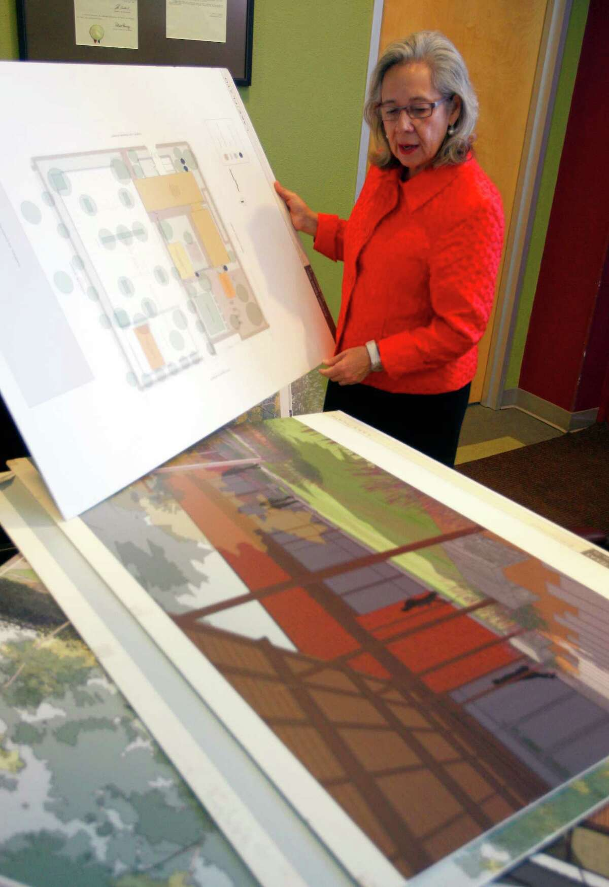 Janie Barrera, CEO of Accion Texas, talks Tuesday Nov. 18, 2014, about the organization's pending name change and upcoming move to a new headquarters building as she shows artist renderings of the new facility.