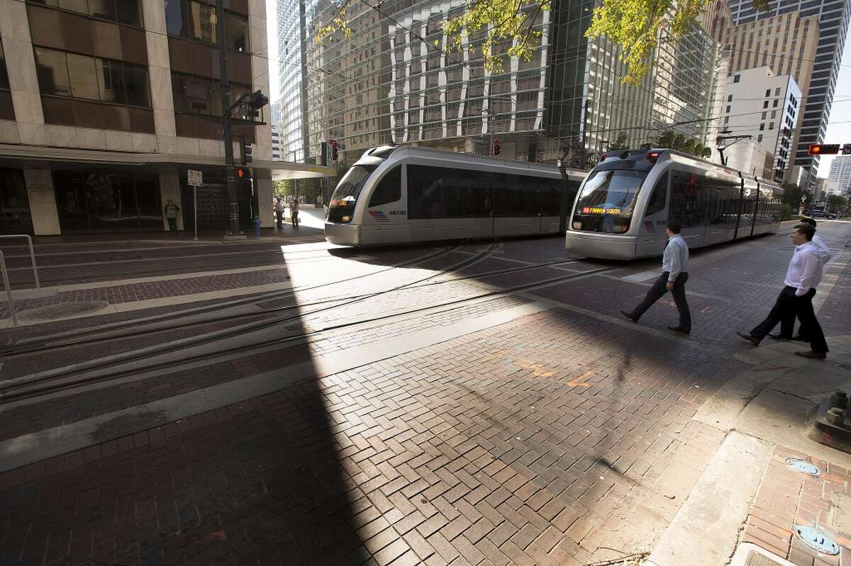 Metro Red Line trains make their way down Main Street at Capitol past the new tracks for the Green and Purple lines on Oct. 22. ( Johnny Hanson / Houston Chronicle )