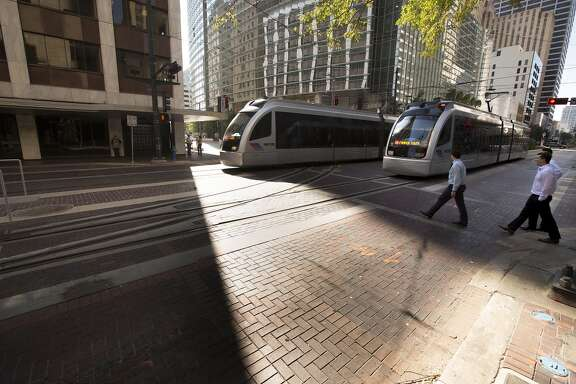 MetroRail Red Line trains make their way down Main Street at Capitol past the new tracks for the Green and Purple Lines Wednesday, Oct. 22, 2014, in Houston. ( Johnny Hanson / Houston Chronicle )