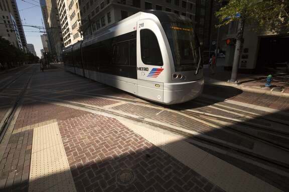 A MetroRail Red Line train makes its way down Main Street at Capitol past the new tracks for the Green and Purple Lines Wednesday, Oct. 22, 2014, in Houston. ( Johnny Hanson / Houston Chronicle )