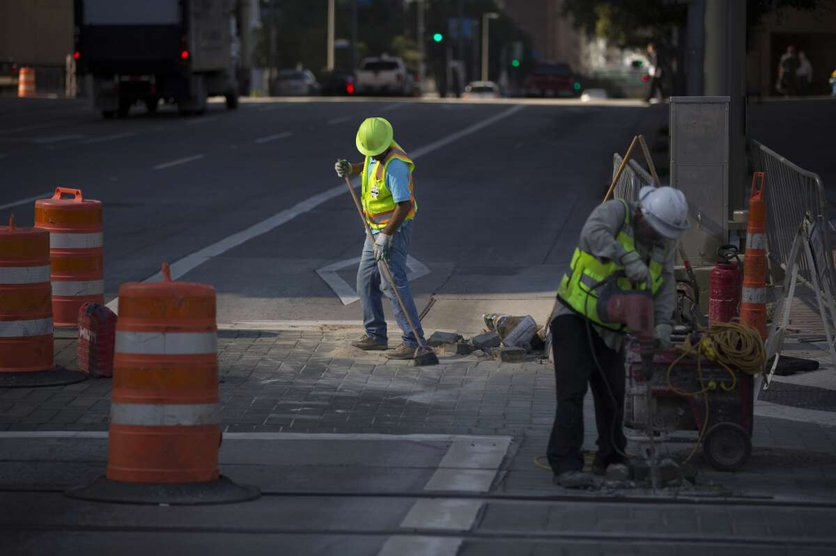 A worker replaces pavers along the new Green and Purple MetroRail lines along Capitol at Smith Street on Oct. 22. ( Johnny Hanson / Houston Chronicle )