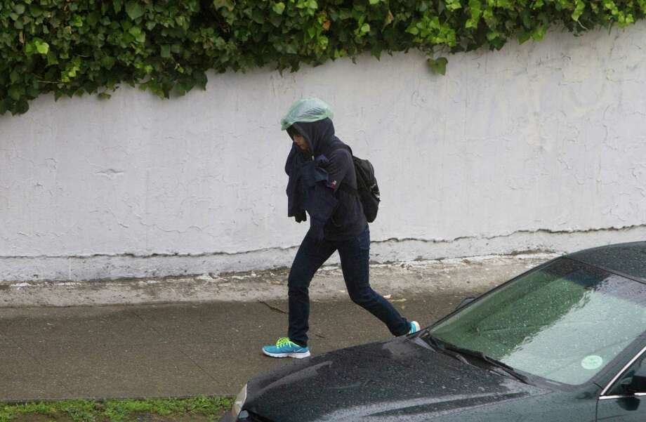 A pedestrian tries to cover her head with a plastic bag from the rain showers passing through the Bay Area on Wednesday. Photo: SF Gate / Douglas Zimmerman