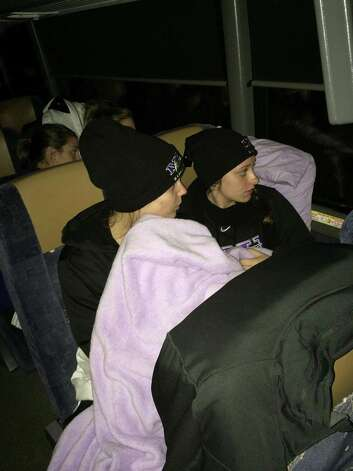 In this photo provided by Niagara's Tiffany Corselli, teammates Gabby Baldasare and Jamie Sherburne huddle under a blanket while stuck on a bus near Buffalo, N.Y., Tuesday, Nov. 18, 2014. The NCAA college basketball team has been stuck on the highway in its bus for nearly 24 hours because of a winter storm that dumped about 4 feet of snow around Buffalo. The team was coming back late Monday night from a loss at Pittsburgh when they were stranded. (AP Photo/Tiffany Corselli) ORG XMIT: NYAG501 Photo: Tiffany Corselli, AP / Tiffany Corselli