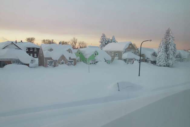 Snow covers a street at daybreak Wednesday, Nov. 19, 2014, in south Buffalo, N.Y. Buffalo-area officials are getting help from a neighboring county in their efforts to clear roads and provide emergency services during the snowstorm that has buried sections of western New York in more than 5 feet of snow. (AP Photo/Carolyn Thompson) ORG XMIT: RPCT701 Photo: Carolyn Thompson, AP / AP