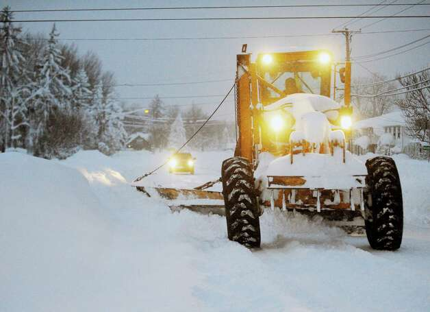 A New York State Snowgrader moves snow on Broadway in Lancaster, N.Y. Wednesday, Nov. 19, 2014. A ferocious storm dumped massive piles of snow on parts of upstate New York, trapping residents in their homes and stranding motorists on roadways, as temperatures in all 50 states fell to freezing or below.   (AP Photo/Gary Wiepert) ORG XMIT: NYGW104 Photo: Gary Wiepert, AP / FR170498 AP
