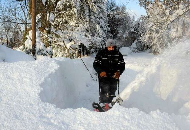 Bob Wilcox clears the snow at the end of his driveway on Bowen Rd. in Lancaster,  N.Y. Wednesday, Nov. 19, 2014.  A ferocious storm dumped massive piles of snow on parts of upstate New York, trapping residents in their homes and stranding motorists on roadways, as temperatures in all 50 states fell to freezing or below.   (AP photo/Gary Wiepert) ORG XMIT: NYGW105 Photo: Gary Wiepert, AP / FR170498 AP