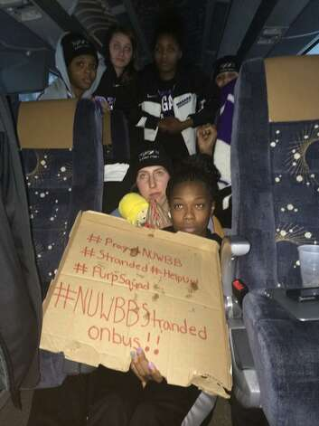 This photo provided by Chelsea Andorka, the Niagara University women's basketball team spokeswoman, shows the team holding a sign while their bus was snowbound on the New York State Thruway in the middle of a lake-effect storm that has dropped more than 4 feet of snow near Lackawanna, N.Y., Tuesday, Nov. 18, 2014. Andorka says the team's bus was headed back from a loss in Pittsburgh when it came to a halt at 2 a.m. Tuesday about two miles from the Lackawanna exit near Buffalo. About 25 people are on the bus, including 15 players plus staff, the coach and coach's family. (AP Photo/Chelsea Andorka)  ORG XMIT: NY125 Photo: Chelsea Andorka, AP / AP