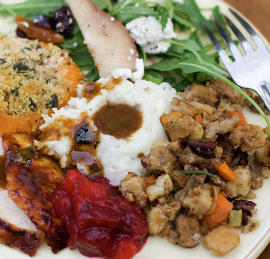 Eat hearty: cider-brined turkey with sage gravy, peach cranberry sauce, mashed potatoes, sausage pecan stuffing, arugula pear salad, sweet potatoes. Photo: Matthew Mead / Associated Press / FR170582