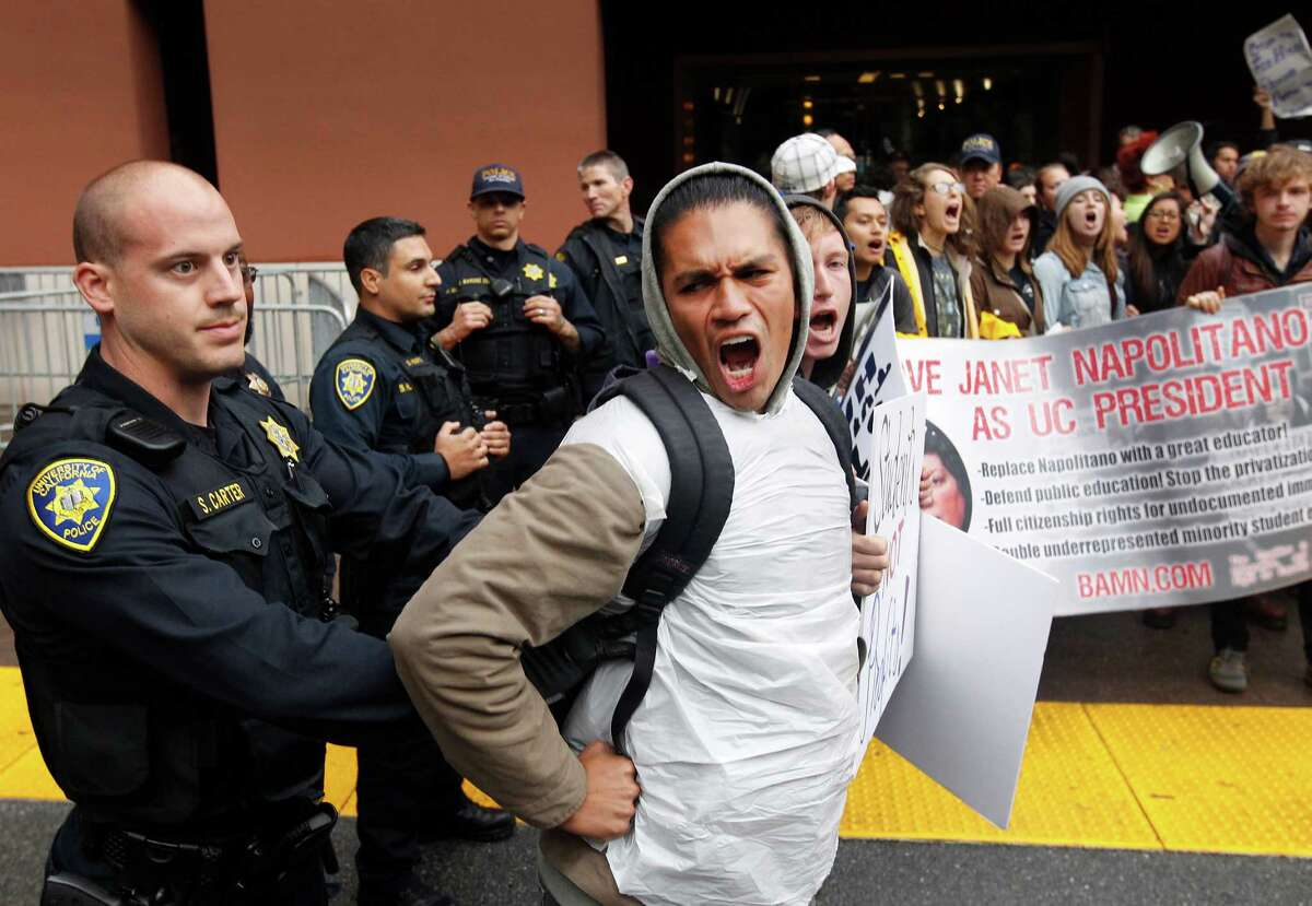 Police officers push interlocked protesters away from the entrance to the University of California Board of Regents meeting in San Francisco, Calif. on Wednesday, Nov. 19, 2014. The regents are considering a systemwide tuition increase.