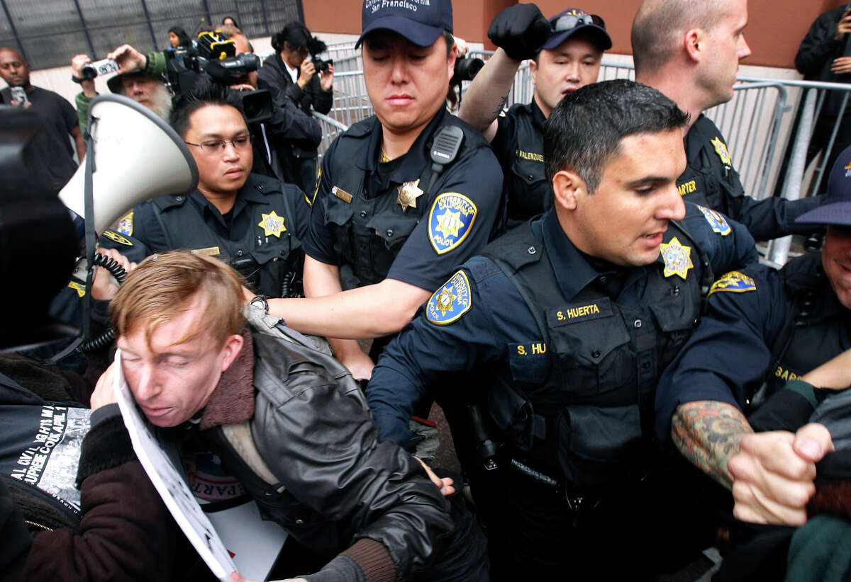 Police officers try to prevent protesters from blocking the entrance to the UC Board of Regents meeting in San Francisco.