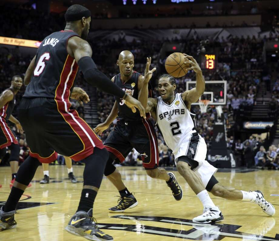 c99182604127 San Antonio Spurs  Kawhi Leonard drives towards the basket around Miami  Heat s LeBron James and