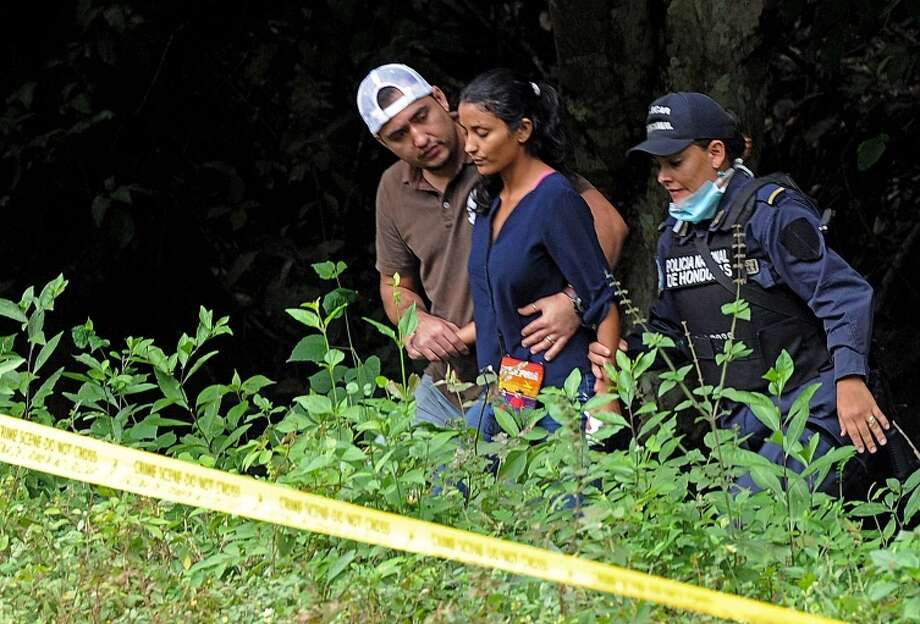 Honduran policemen comfort Kory Alvarado (C), after she identified the bodies of her sisters former Miss Honduras Maria Jose Alvarado and Sofia Trinidad, in the banks of the Aguagua river in the La Arada-Caulotales road in the Santa Barbara department, 200 km northwest of Tegucigalpa. The two women were missing since last November 13 after attending a birthday party at Aguagua thermal resort.   AFP PHOTO/Orlando SIERRA.ORLANDO SIERRA/AFP/Getty Images Photo: ORLANDO SIERRA / AFP/Getty Images / AFP