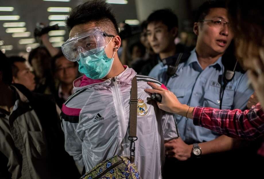 Police detain a man wearing protective gear as pro-democracy protesters face off with police. Photo: ALEX OGLE / AFP/Getty Images / AFP