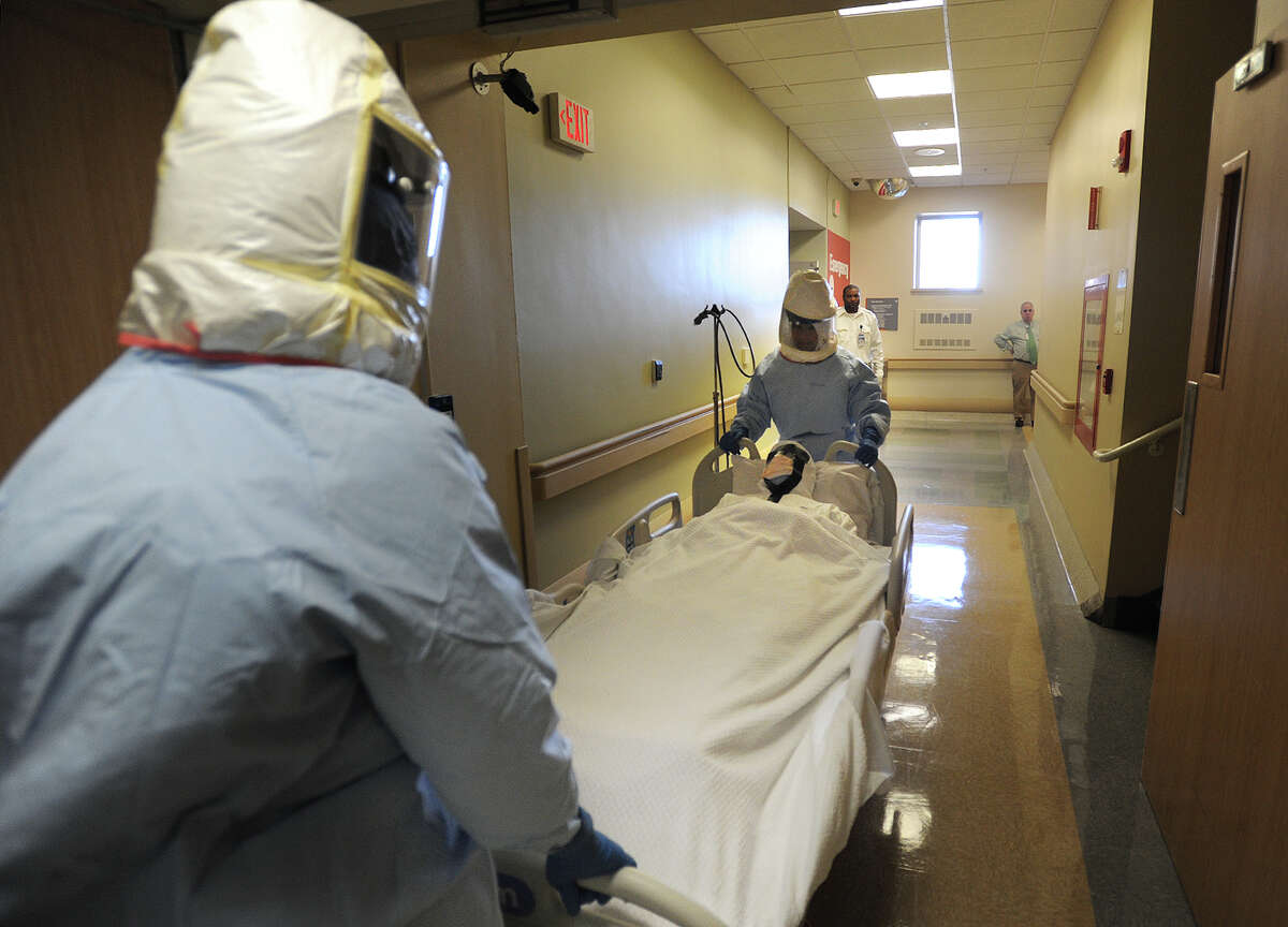 A man posing as an Ebola patient is transported to a secure room in the Medical ICU during a surprise Ebola drill at Bridgeport Hospital in Bridgeport, Conn. on Wednesday, November 19, 2014.
