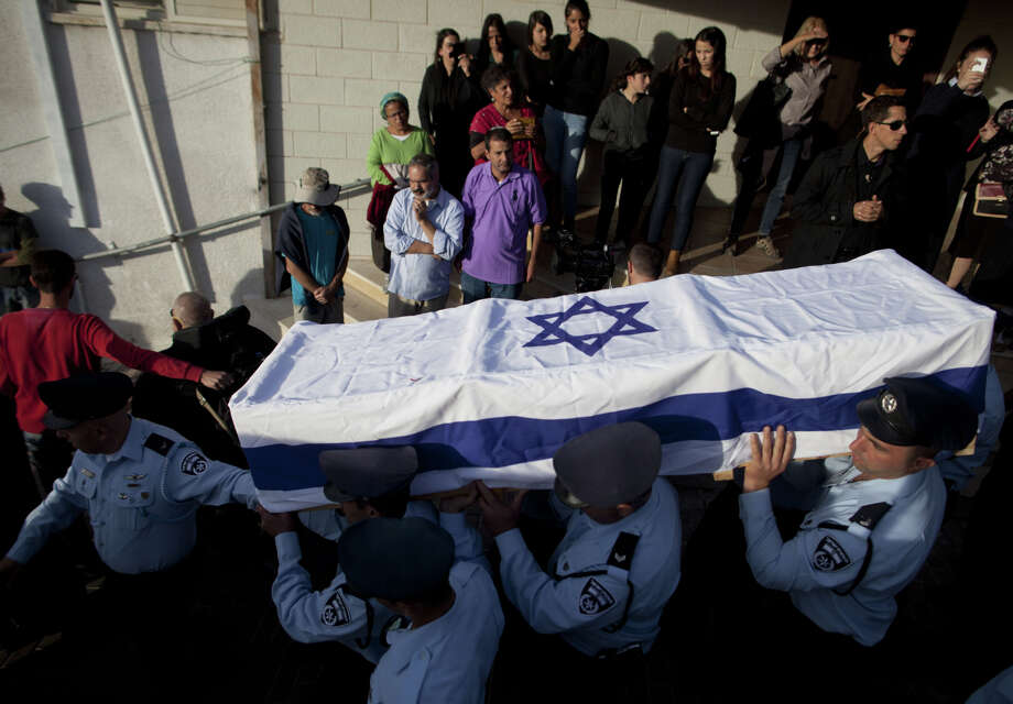 Israeli police officers carry the flag-draped coffin of Israeli police officer Zidan Sif during his funeral in Yanuh-Jat. Sif died Tuesday from his wounds in the synagogue attack. Photo: Lior Mizrahi / Getty Images / 2014 Getty Images