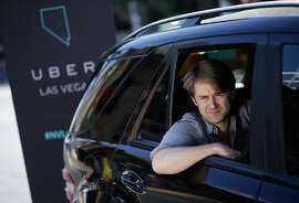 Uber West Coast Regional Manager William Barnes poses for pictures in the back of a car in Las Vegas.