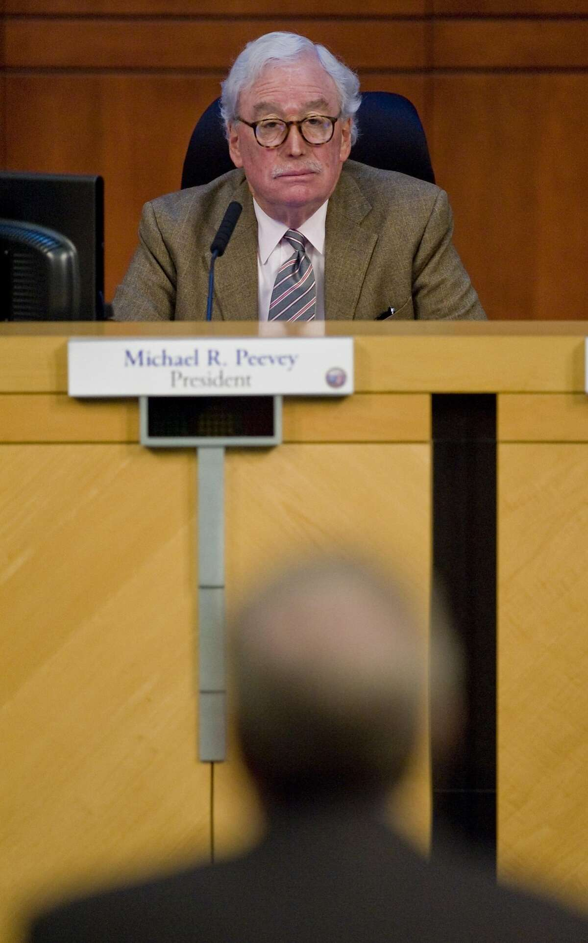 FILE - In this Thursday, Oct. 25, 2012 file photo, Michael Peevey, president of the California Public Utilities Commission, listens to a speaker at Irvine City Hall in Irvine, Calif. Peevey, California's chief utility regulator, under fire over accusations of secret dealings with the state's largest utility, said Thursday, Oct. 9, 2014 that he will not seek reappointment when his term ends at the end of the year. (AP Photo/The Orange County Register, Mark Rightmire, File) MAGS OUT; LOS ANGELES TIMES OUT