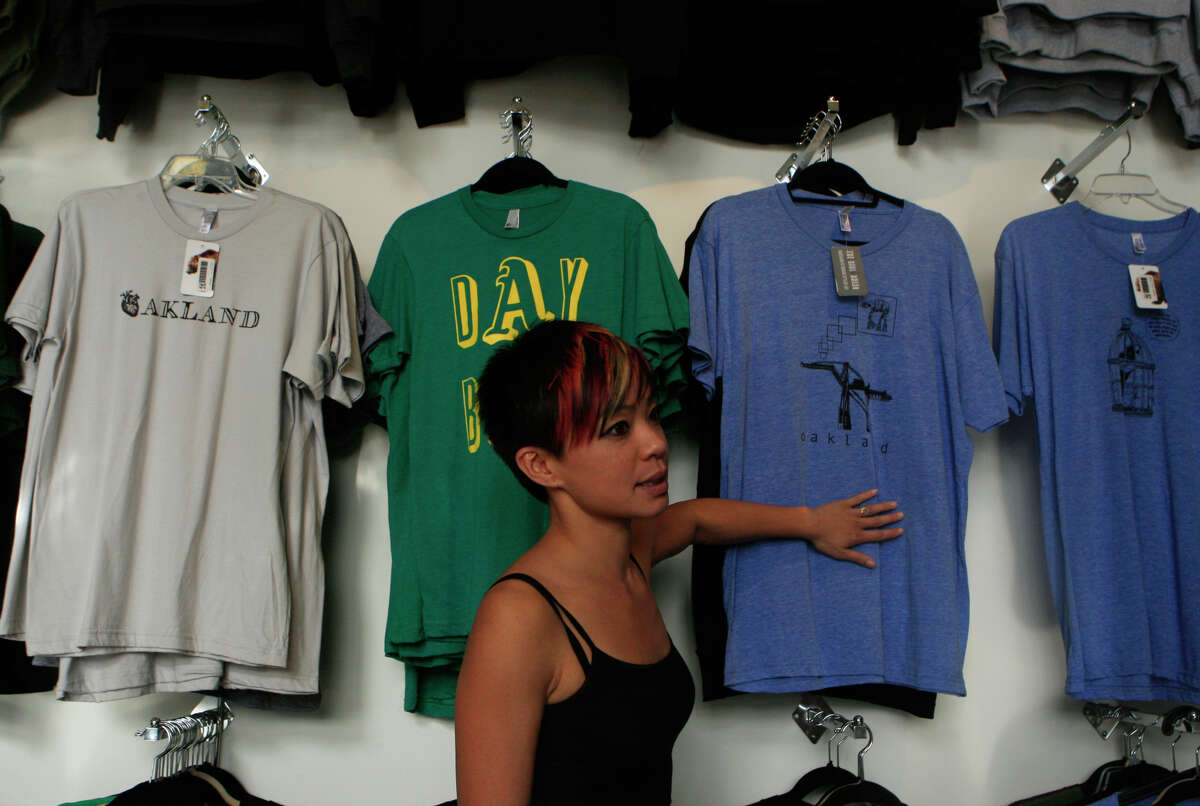 Loretta Nguyen, owner of LuckyLo, shows some of the more popular Oakland-inspired shirts sold in her store.