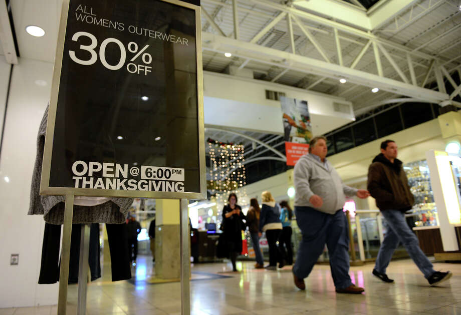 Shoppers pass by a store's sign saying it will be open on Thanksgiving Day at Westfield's Connecticut Post Mall in Milford, Conn., on Wednesday Nov. 19, 2014. Some shoppers have expressed displeasure at the idea of stores and malls being open on a holiday which was when stores traditionally closed. Photo: Christian Abraham / Connecticut Post