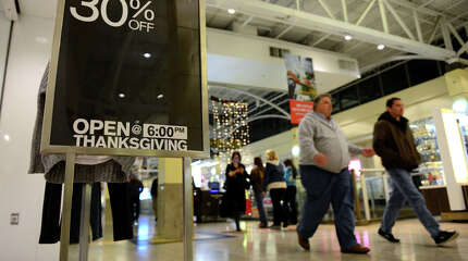 Shoppers pass by a store's sign saying it will be open on Thanksgiving Day at Westfield's Connecticut Post Mall in Milford, Conn., on Wednesday Nov. 19, 2014. Some shoppers have expressed displeasure at the idea of stores and malls being open on a holiday which was when stores traditionally closed.
