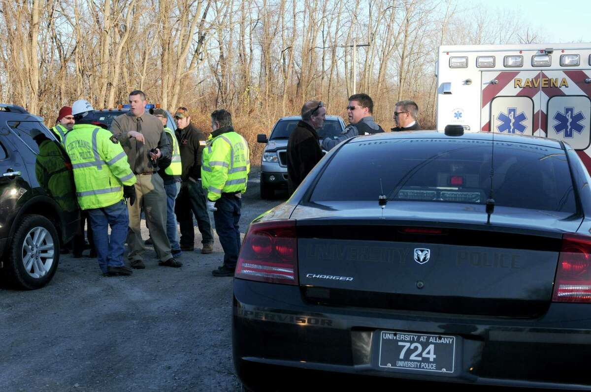 Police and rescue personnel gather at a railroad access road to coordinate recovery efforts for a body found along the Hudson River Wednesday afternoon, Nov. 19, 2014, in Coeymans, N.Y. (Michael P. Farrell/Times Union)