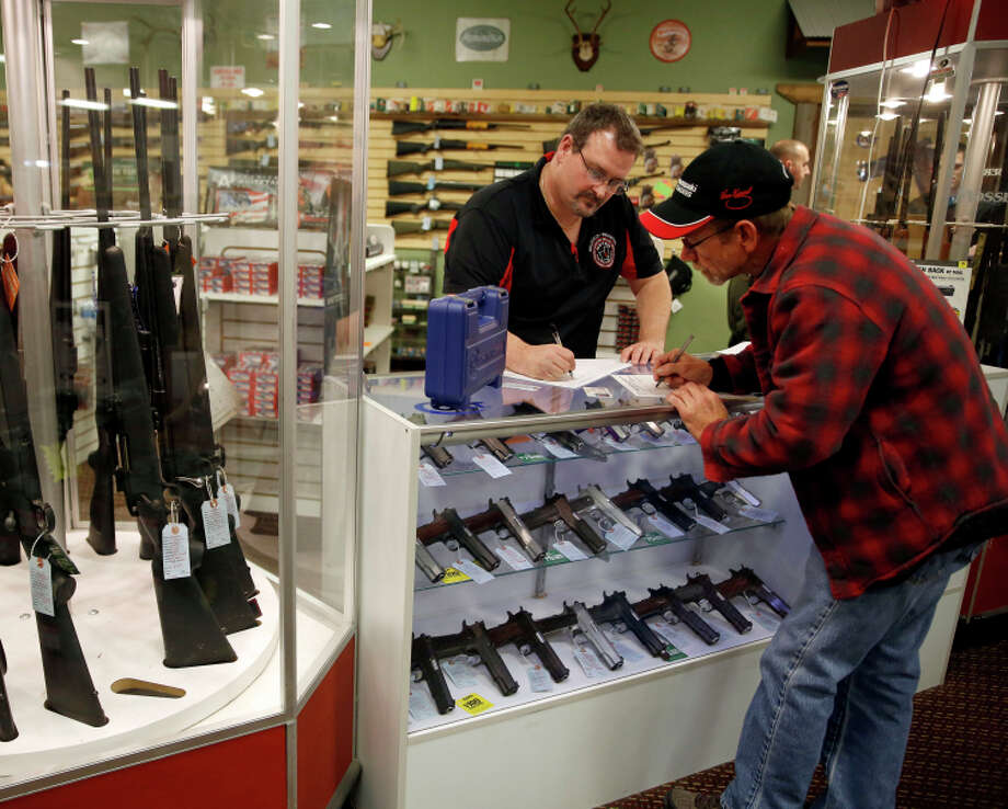Steven King fills out paperwork for a sale to a first-time gun owner at his store in Bridgeton, Mo. Photo: Jeff Roberson / Associated Press / AP