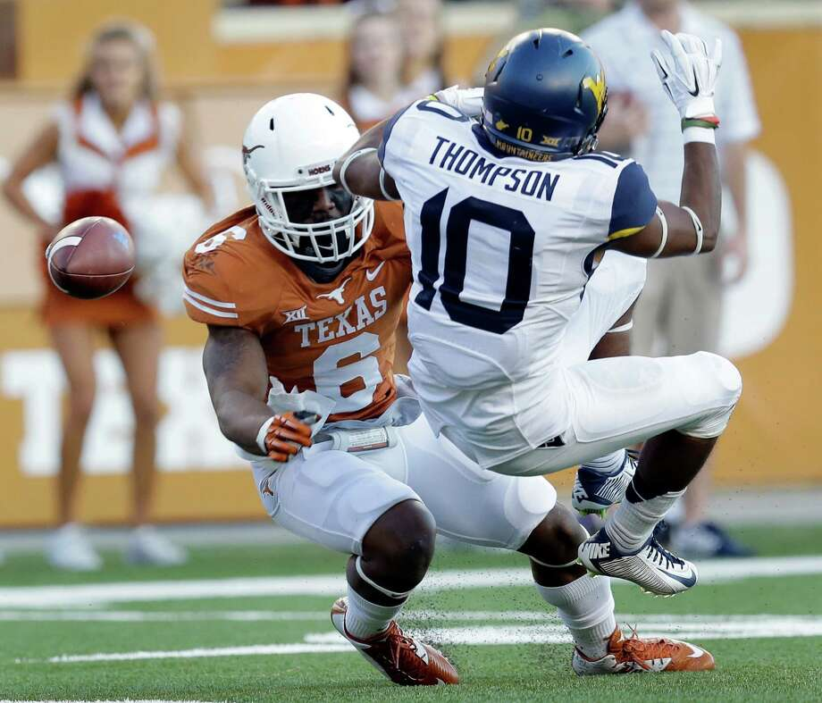 Texas' Quandre Diggs (6) breaks up a pass intended for West Virginia's Jordan Thompson (10) during the second half on Nov. 8, 2014, in Austin. Texas won 33-16. Photo: Eric Gay, STF / Associated Press / AP