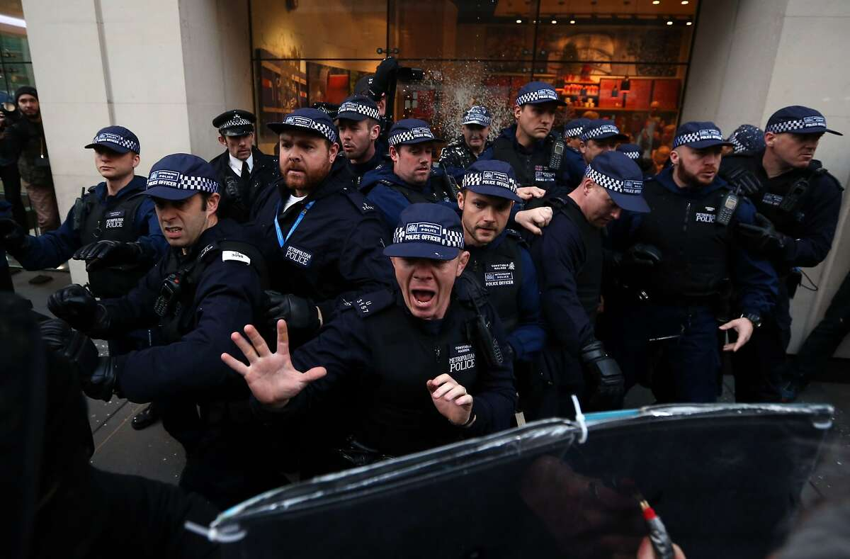 LONDON, ENGLAND - NOVEMBER 19: Police officers shout at protesters during a demonstration against fees and cuts in the education system on November 19, 2014 in London, England. A coalition of student groups have organised a day of nationwide protests in support of free education and to campaign against cuts. Photo by Carl Court/Getty Images) (Photo by Carl Court/Getty Images) *** BESTPIX ***