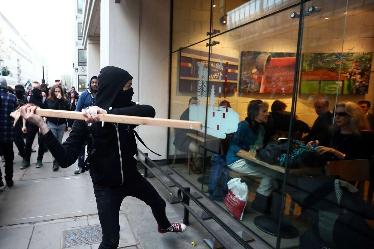 LONDON, ENGLAND - NOVEMBER 19: A protester attempts to smash a Starbucks window during a demonstration against fees and cuts in the education system on November 19, 2014 in London, England. A coalition of student groups have organised a day of nationwide protests in support of free education and to campaign against cuts. Photo by Carl Court/Getty Images) (Photo by Carl Court/Getty Images) *** BESTPIX ***