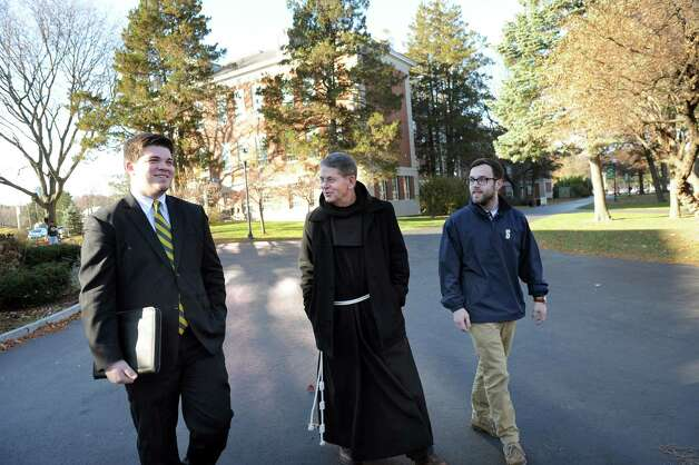 Siena College's new president Brother Ed Coughlin, center, walks with Patrick Madden, 20, student senate communications director, left, and Andy Murphy, 20, sophomore class president, on Wednesday, Nov. 19, 2014, at Siena College in Loudonville, N.Y.  (Cindy Schultz / Times Union) Photo: Cindy Schultz / 00029558A
