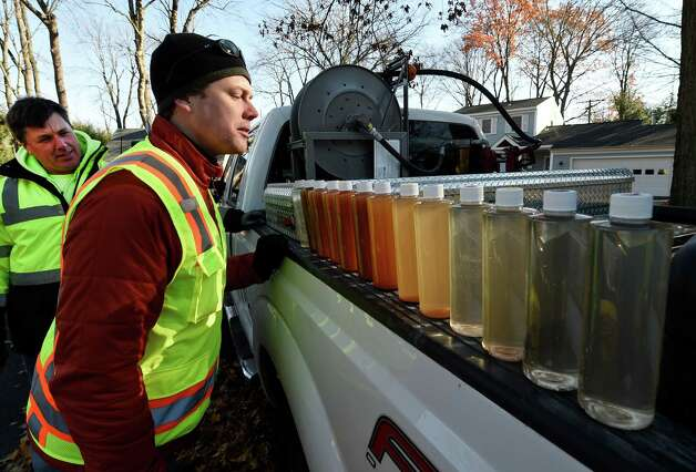Andy Boniewski, left, and Andrew Kohout of the Town of Scotia DPW look at the end result of a demonstration of the ice pigging process Wednesday morning, Nov. 19, 2014 in Bethlehem, N.Y. The use of ice slurry injected into the water mains, called ice pigging, acts as an efficient way to clean the supply pipes. The Town of Bethlehem is the first in the State to use this method. (Skip Dickstein/Times Union) Photo: SKIP DICKSTEIN / 00029522A