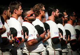 Pablo Sandoval (third from left) listens to the Anthem at a playoff game in early October — the month when he's at his best.