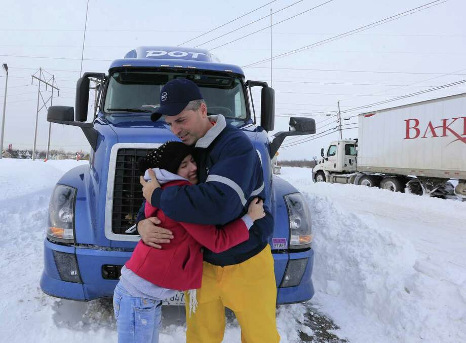 Charles Miller a tractor trailor driver for DOT foods hugs and says goodbye to  Hope Clingan, a college student from Cuyahoga Community College in Ohio along camp road in Hamburg, N.Y.,  on Wednesday, Nov. 19, 2014. Miller carried Clingan thru the snow to her hotel  on Tuesday evening.  A ferocious lake-effect storm left the Buffalo area buried under 6 feet of snow Wednesday, trapping people on highways and in homes, and another storm expected to drop 2 to 3 feet more was on its way. (AP Photo/The Buffalo News, Harry Scull Jr.)  TV OUT; MAGS OUT; MANDATORY CREDIT; BATAVIA DAILY NEWS OUT; DUNKIRK OBSERVER OUT; JAMESTOWN POST-JOURNAL OUT; LOCKPORT UNION-SUN JOURNAL OUT; NIAGARA GAZETTE OUT; OLEAN TIMES-HERALD OUT; SALAMANCA PRESS OUT; TONAWANDA NEWS OUT    ORG XMIT: NYBUE127 Photo: Harry Scull Jr. / The Buffalo News
