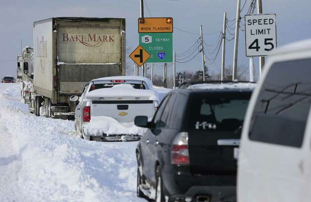 Vehicles sit at a closed New York State Thruway entrance in Hamburg, N.Y. on Wednesday, Nov. 19, 2014. A ferocious lake-effect storm left the Buffalo area buried under 6 feet of snow Wednesday, trapping people on highways and in homes, and another storm expected to drop 2 to 3 feet more was on its way. (AP Photo/The Buffalo News, Harry Scull Jr.)  TV OUT; MAGS OUT; MANDATORY CREDIT; BATAVIA DAILY NEWS OUT; DUNKIRK OBSERVER OUT; JAMESTOWN POST-JOURNAL OUT; LOCKPORT UNION-SUN JOURNAL OUT; NIAGARA GAZETTE OUT; OLEAN TIMES-HERALD OUT; SALAMANCA PRESS OUT; TONAWANDA NEWS OUT    ORG XMIT: NYBUE121 Photo: Harry Scull Jr. / The Buffalo News