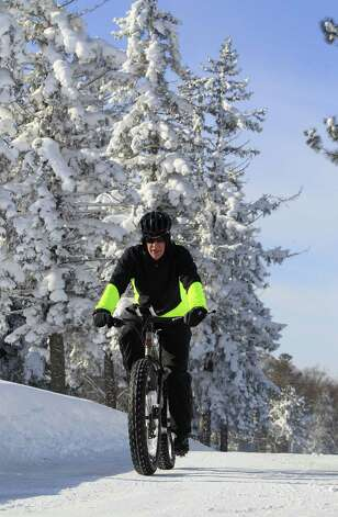 Bill Graves rides his bike on the snow at Chrsnut Ridge Park, Orchard Park,NY on Wednesday, Nov. 19, 2014.  A ferocious lake-effect storm left the Buffalo area buried under 6 feet of snow Wednesday, trapping people on highways and in homes, and another storm expected to drop 2 to 3 feet more was on its way. (AP Photo/The Buffalo News, Harry Scull Jr.)  TV OUT; MAGS OUT; MANDATORY CREDIT; BATAVIA DAILY NEWS OUT; DUNKIRK OBSERVER OUT; JAMESTOWN POST-JOURNAL OUT; LOCKPORT UNION-SUN JOURNAL OUT; NIAGARA GAZETTE OUT; OLEAN TIMES-HERALD OUT; SALAMANCA PRESS OUT; TONAWANDA NEWS OUT   ORG XMIT: NYBUE106 Photo: Harry Scull Jr. / The Buffalo News