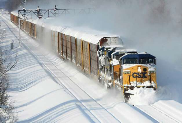 A CSX freight train plows its way past the Cemetery Rd. overpass in Lancaster,  N.Y. Wednesday, Nov. 19, 2014. A lake-effect snow storm dumped over five feet of snow in areas across Western New York. Another two to three feet of snow is expected in the area, bringing snow totals to over 100 inches, almost a years' worth of snow in three days.  (AP Photo/Gary Wiepert) ORG XMIT: NYGW107 Photo: Gary Wiepert / FR170498 AP