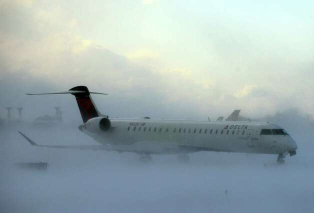 A plane negotiates its way through the snow at the Buffalo Niagara International Airport in Buffalo, N.Y., as a lake-effect snowstorm with freezing temperatures hit the area Tuesday, Nov. 18, 2014. Temperatures fell to freezing or below at recording stations in all 50 states on Tuesday morning, from the highest elevations in the mountains of Hawaii to the snow-paralyzed Buffalo area in New York. (AP Photo/Gary Wiepert) ORG XMIT: NYGW101 Photo: Gary Wiepert / FR170498 AP