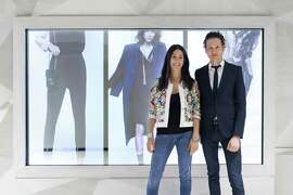 Designer Rebecca Minkoff with company CEO, Uri Minkoff, in front of the three screens that make up the store's connected wall.