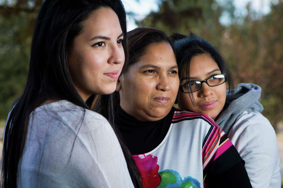 Maria Espinoza, center, is embraced by her daughters Glenda Moreno, left, and Wendy Moreno, both U.S. citizens. Espinoza, who crossed the border years ago, said she hopes the president will bring good news.