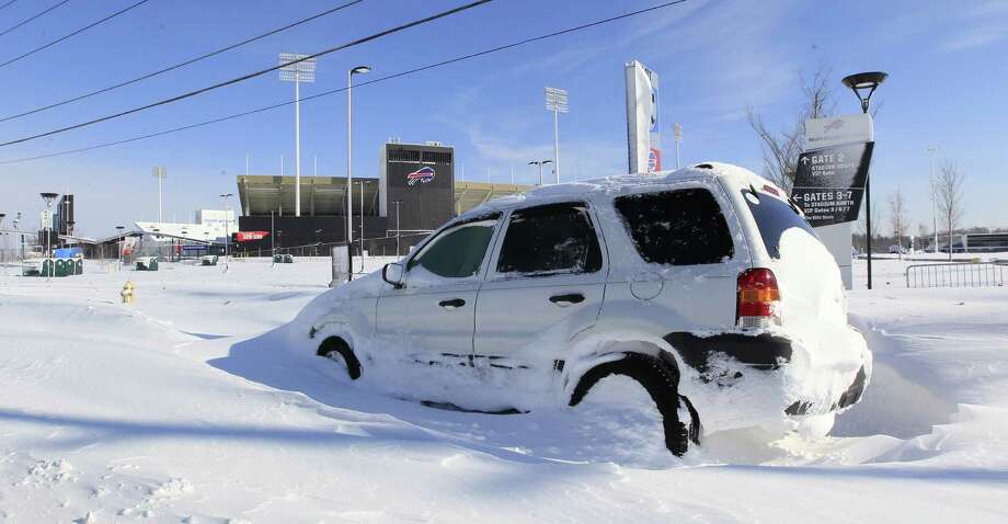 An abandoned car sits infront of a snow covered Ralph Wilson Stadium home of the Buffalo Bills in Orchard Park, N.Y. on Wednesday, Nov. 19, 2014.  A ferocious lake-effect storm left the Buffalo area buried under 6 feet of snow Wednesday, trapping people on highways and in homes, and another storm expected to drop 2 to 3 feet more was on its way. (AP Photo/The Buffalo News, Harry Scull Jr.)  TV OUT; MAGS OUT; MANDATORY CREDIT; BATAVIA DAILY NEWS OUT; DUNKIRK OBSERVER OUT; JAMESTOWN POST-JOURNAL OUT; LOCKPORT UNION-SUN JOURNAL OUT; NIAGARA GAZETTE OUT; OLEAN TIMES-HERALD OUT; SALAMANCA PRESS OUT; TONAWANDA NEWS OUT   ORG XMIT: NYBUE105 Photo: Harry Scull Jr. / The Buffalo News