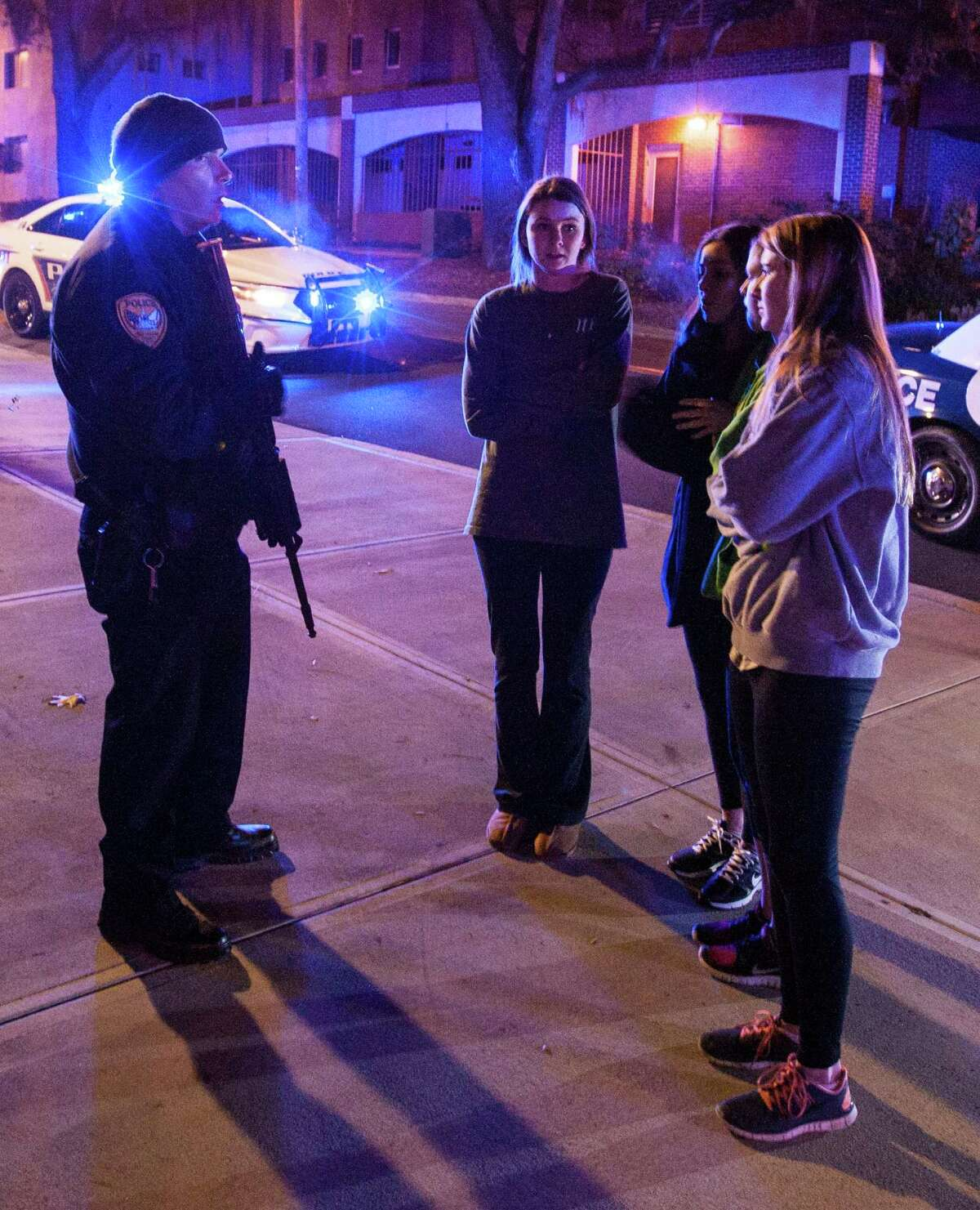 A Tallahassee police officer talks to several students outside the Strozier library on the Florida State University campus in Tallahassee, FL. where a shooting occurred Thursday Nov 20, 2014. The gunman was shot and killed by police officers.