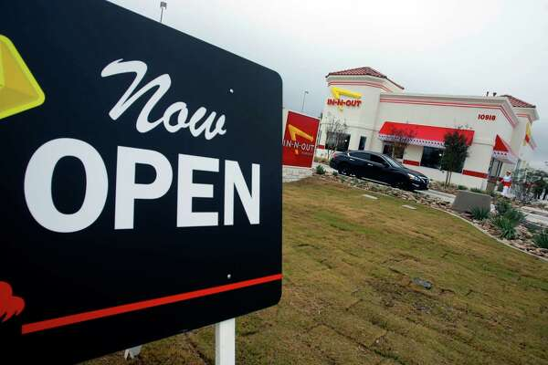 A sign calls attentition to the grand opening Thursday Nov. 20, 2014 of San Antonio's first In-N-Out Burger. The store, located on Culebra just outside Loop 1604, opened at 9 a.m. because of the large crowds of people already in line for the store's normal 10 a.m. opening.