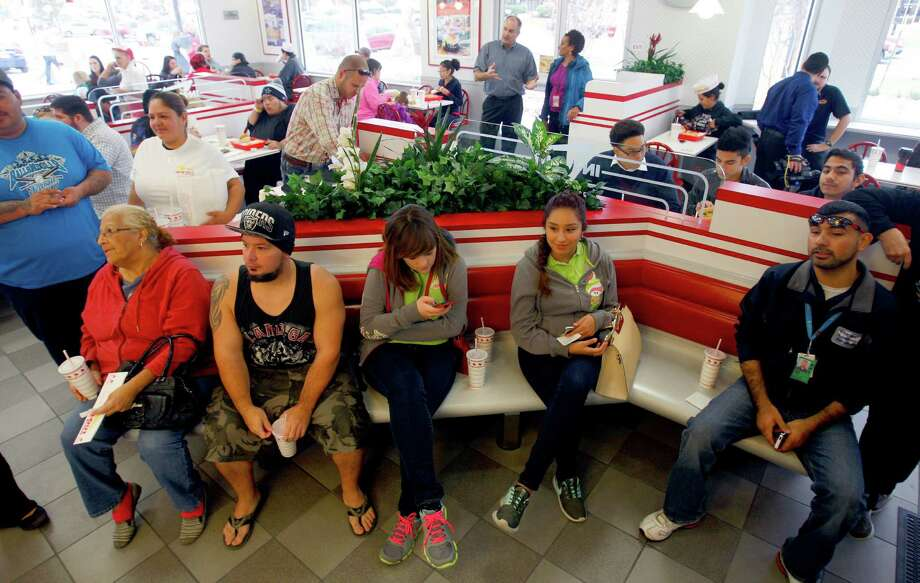 People wait for their order number to e called while they attend the grand opening Thursday Nov. 20, 2014 of San Antonio's first In-N-Out Burger. The store, located on Culebra just outside Loop 1604, opened at 9 a.m. because of the large crowds of people already in line for the store's normal 10 a.m. opening. Photo: William Luther, San Antonio Express-News / © 2014 San Antonio Express-News
