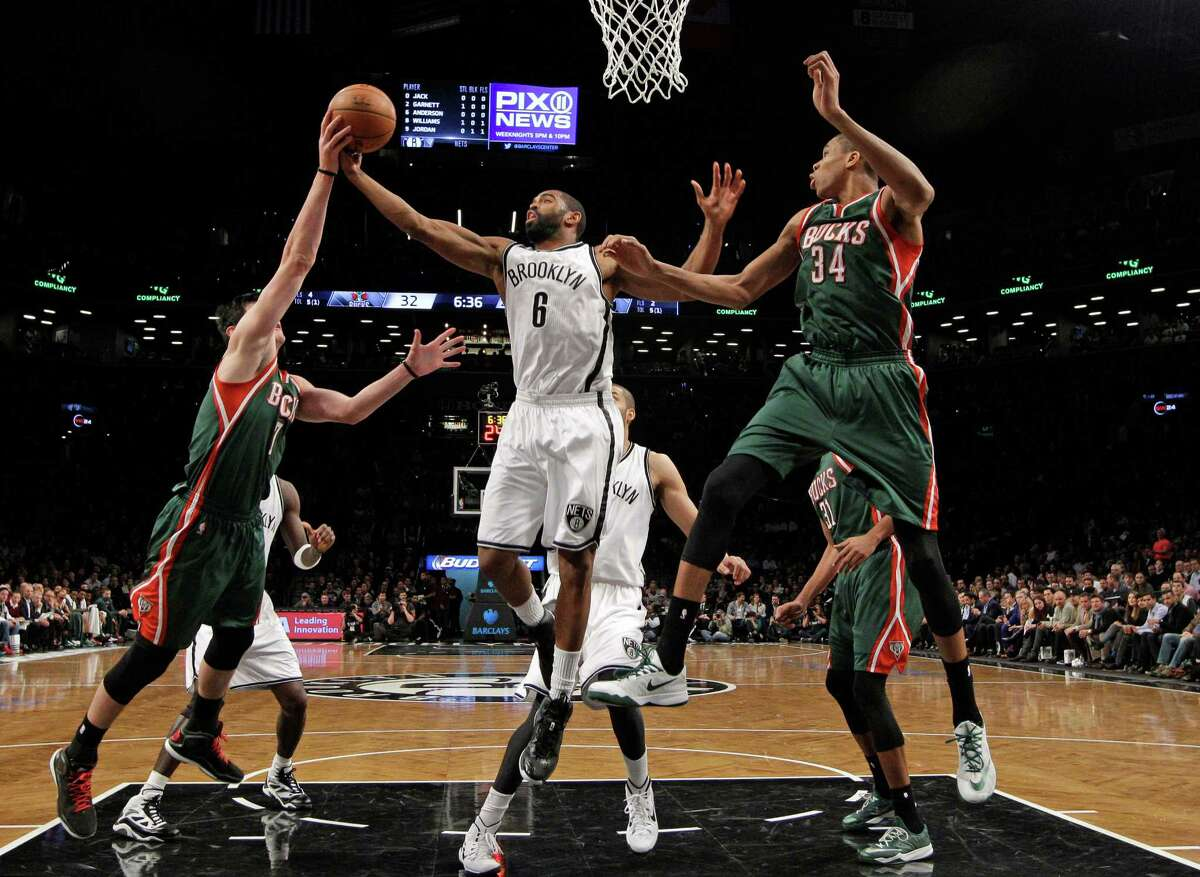 Milwaukee Bucks forward Ersan Ilyasova (7) gets a hand on the ball held by Brooklyn Nets guard Alan Anderson (6) with Bucks guard Giannis Antetokounmpo (34) defending during the first half of an NBA basketball game Wednesday, Nov. 19, 2014, in New York. (AP Photo/Kathy Willens) ORG XMIT: NYKW112